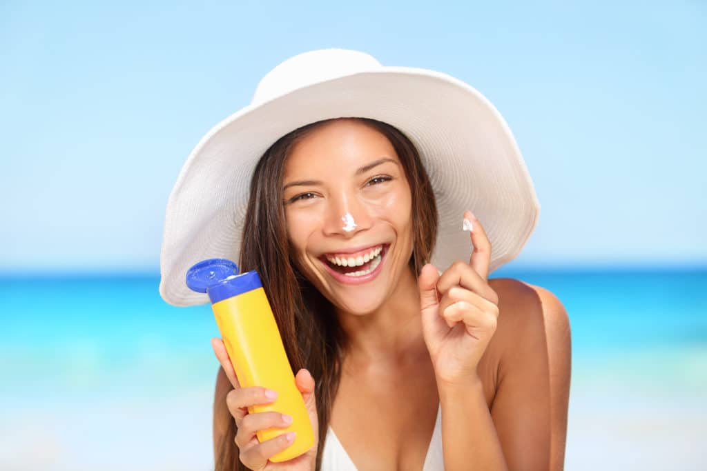 woman applying suntan lotion showing bottle
