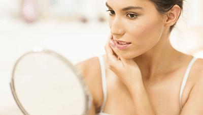 Female checking skin in mirror