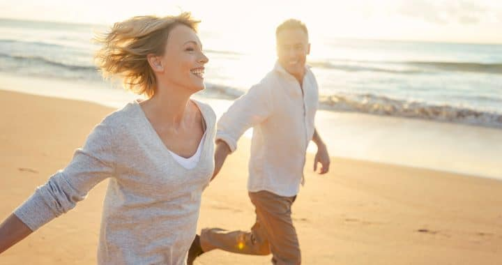 mature couple running beach